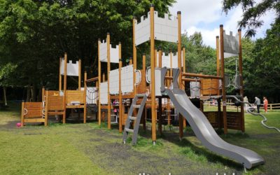 Large castle themed climbing frame with wavy slide in the play area at Daventry Country Park