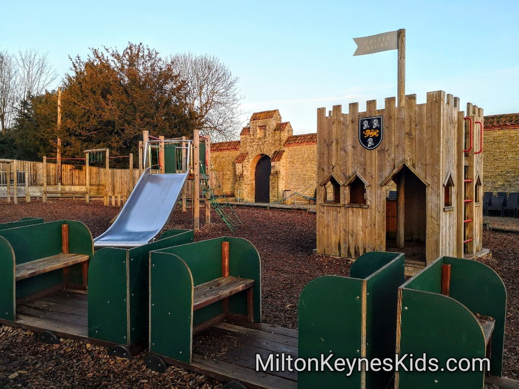 Wooden castle play equipment, train and slide in the play area at Castle Ashby Gardens